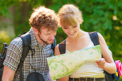 Hiking backpacking couple reading map on trip. Royalty Free Stock Photography