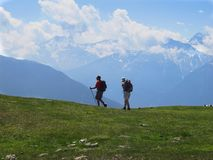 Hiking backpacking walking on mountain ridge in the Alps. South Tirol, Italy - June 17, 2013: Two hikers with backpacks walk across the grassy summit of Spitzige Royalty Free Stock Image