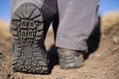 Hiking boot closeup on mountain rocks. Royalty Free Stock Image