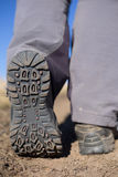 Hiking boot closeup on mountain rocks. Stock Photo