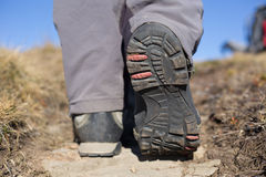 Hiking boot closeup on mountain rocks. Stock Photos