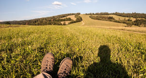 Hiking boot and photographer shadow on meadow with hill on the background Stock Photos