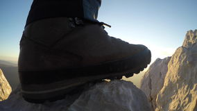 Hiking boot on the rock in sunset stock footage