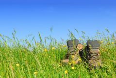 Hiking boots. In green meadow with blue sky background Stock Photography