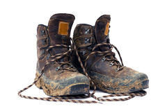 Hiking boots. A pair of dirty hiking boots on white background Royalty Free Stock Photos