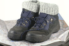 Hiking boots. Pair of blue hiking boots resting on a map white background Royalty Free Stock Images