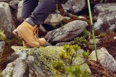Hiking boots close-up. girl tourist steps on the mountain trail on the rocks. Travel and active life concept Royalty Free Stock Image