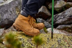 Hiking boots close-up. girl tourist steps on the mountain trail on the rocks. stock photography