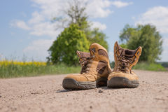 Hiking boots. On a dusty dirt road Royalty Free Stock Photography