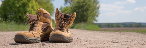 Hiking boots. On a dusty dirt road Stock Images