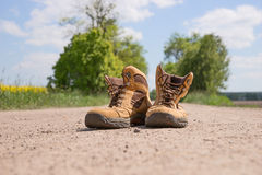 Hiking boots. On a dusty dirt road Stock Image
