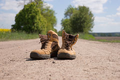 Hiking boots. On a dusty dirt road Stock Photo