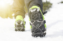 Hiking boots with equipment for ice. Snow like a background and sun. Sun is shining. Moutains and travel. Hiking boots with equipment for ice. Snow like a Royalty Free Stock Images