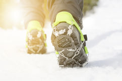 Hiking boots with equipment for ice. Snow like a background and sun. Sun is shining. Moutains and travel. Royalty Free Stock Photos