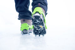 Hiking boots with equipment for ice. Snow like a background and sun. Sun is shining. Moutains and travel. Hiking boots with equipment for ice. Snow like a Stock Photos