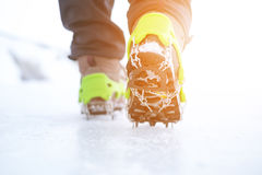 Hiking boots with equipment for ice. Snow like a background and sun. Sun is shining. Moutains and travel. Hiking boots with equipment for ice. Snow like a Royalty Free Stock Photography