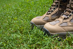 Hiking Boots in Grass. Worn hiking boots standing in green grass Stock Images