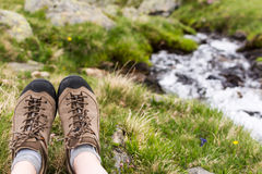 Hiker resting on a green grass with a view on mountain river on bokeh background. Stock Photo