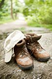 Hiking boots and hat in the woods Stock Photos