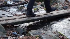 Hiking boots, hiker goes on a Board over stream. stock footage