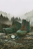 Hiking boots with knife and compass on tree log Royalty Free Stock Image