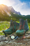 Hiking boots with knife on tree trunk Royalty Free Stock Photo