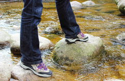 Hiking boots and legs of a woman over a mountain stream Royalty Free Stock Photography