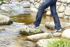 Hiking boots and legs of a woman over a mountain stream Royalty Free Stock Image