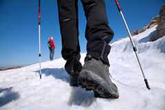 Hiking boots on the mountain trail in the snow. Hiking boots on the mountain trail royalty free stock photos