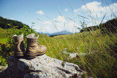 Hiking Boots. Old hiking boots on rock in the mountains Royalty Free Stock Image