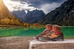 Hiking Boots On Wooden Bench At Landro Lake In The Dolomites Mountains In Italy. Italian Landscape Or Scenery. Royalty Free Stock Photography