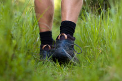 Hiking boots in an outdoor action. Closeup of a hiking shoes in a grass Royalty Free Stock Images