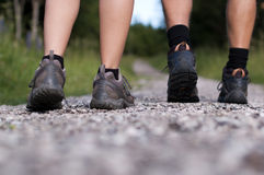 Hiking boots in an outdoor action. Closeup of two pairs of hiking boots on a trail Royalty Free Stock Images