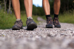 Hiking boots in an outdoor action. Closeup of two pairs of hiking boots on a trail Royalty Free Stock Photography