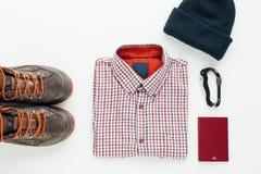 Hiking boots, plaid shirt, wool cap and carabiner Stock Photos
