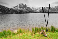Hiking boots and poles on mountain lake Stock Image