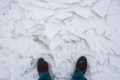 Hiking boots on river cracked snow, top view. Concept of danger  an exit to weak ice Stock Images