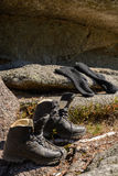 Hiking boots and socks on the rock Stock Photos