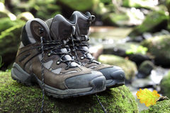 Hiking boots by stream in a forest Stock Photos