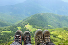 Hiking boots of traveler sitting on high mountain top Stock Photos