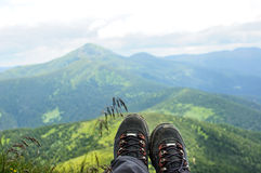 Hiking boots of traveler sitting on high mountain top Stock Photo