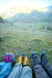 Hiking boots of traveler sitting on high mountain top in travel royalty free stock photography