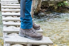 Hiking boots on tree trunk bridge over a creek stock photography
