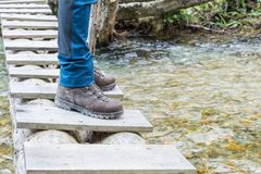 Hiking boots on tree trunk bridge over a creek royalty free stock photos