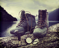 Hiking boots on tree trunk near lake Royalty Free Stock Images