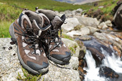 Hiking boots by waterfall in a stream Royalty Free Stock Photos