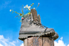 Hiking boots on a wooden stake royalty free stock photography