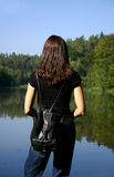 Hiking break. Female hiker looking out on a forest lake royalty free stock image
