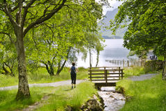 Hiking beside Buttermere. A female hiker approaching a wooden bridge over a stream on the shore of Buttermere in the English Lake District royalty free stock photos