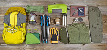 Hiking and camping gear organized on rustic wooden boards. High angled view of organized hiking gear placed on rustic wooden boards in rectangle format Royalty Free Stock Images